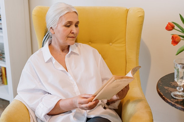 elderly woman reading a book in a chair